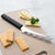 Rada Cutlery Cheese knife with black handle on cutting board with cheese slices.