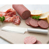 Cook's Utility knife with silver handle on cutting board by sliced sausage.