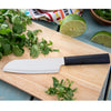 Cook's Utility knife with black handle on wooden cutting board with herbs.