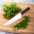 Rada Cutlery French Chef knife with black handle and minced herbs.