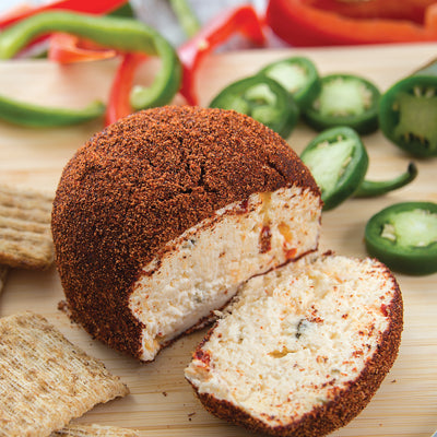 Sweet Hot Pepper Jelly Cheeseball sliced with crackers and jalapenos.