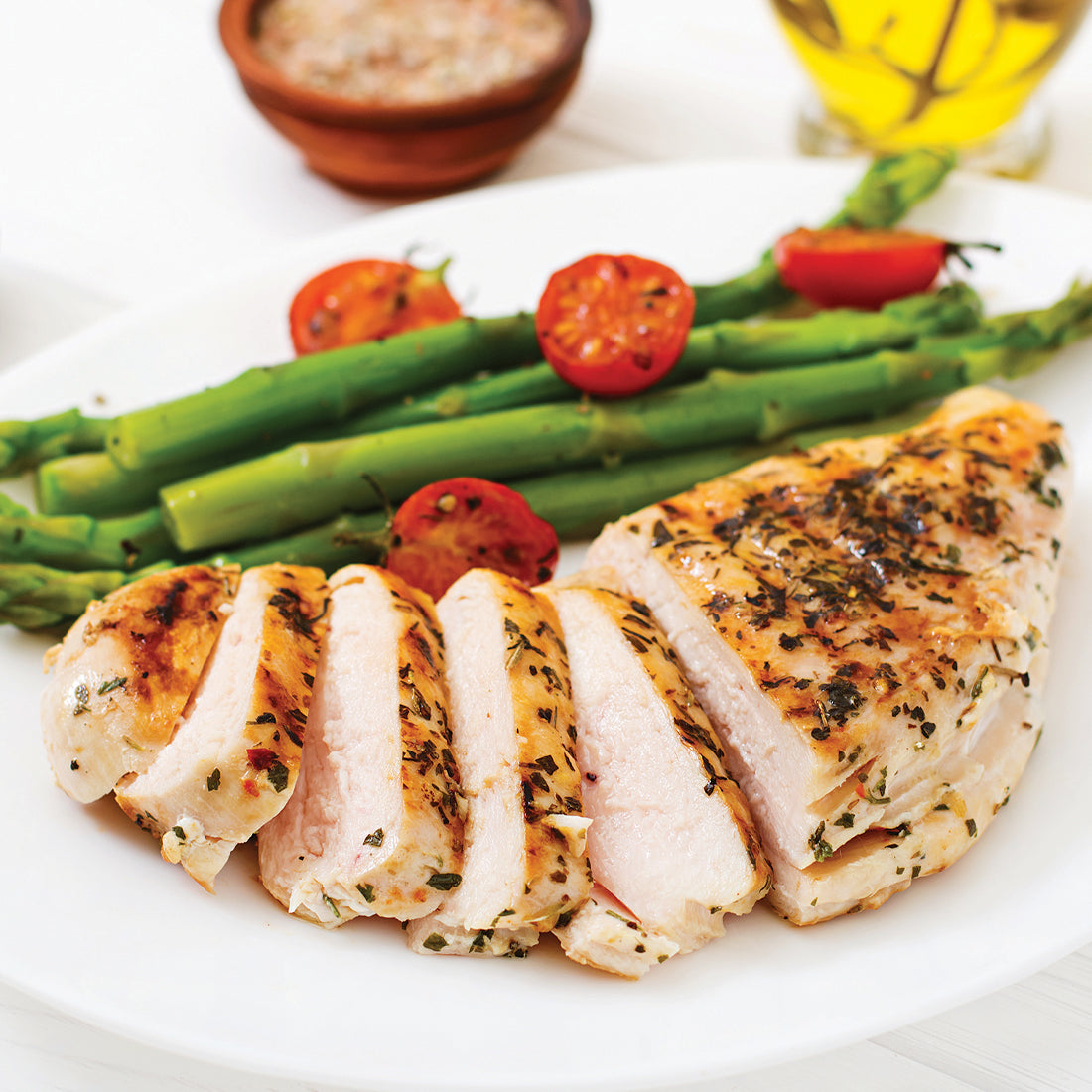 Italian Herb & Garlic Marinade shown on grilled chicken served with asparagus.