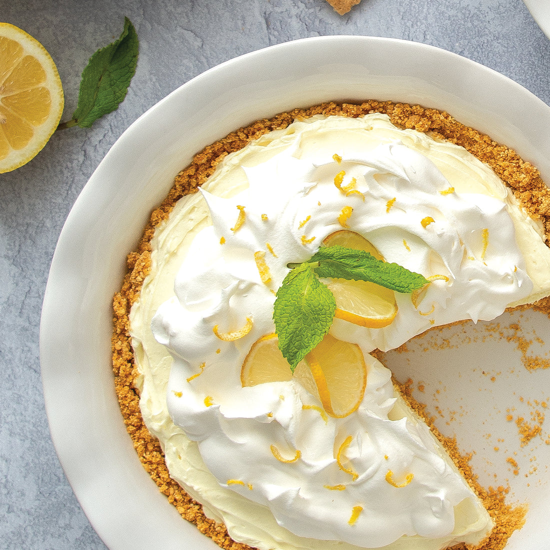 Lemon Drop No-Bake Cheesecake in pie dish garnished with lemon zest and mint.