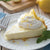Lemon Drop No-Bake Cheesecake in pie dish garnished with lemon slices, lemon zest, and mint.