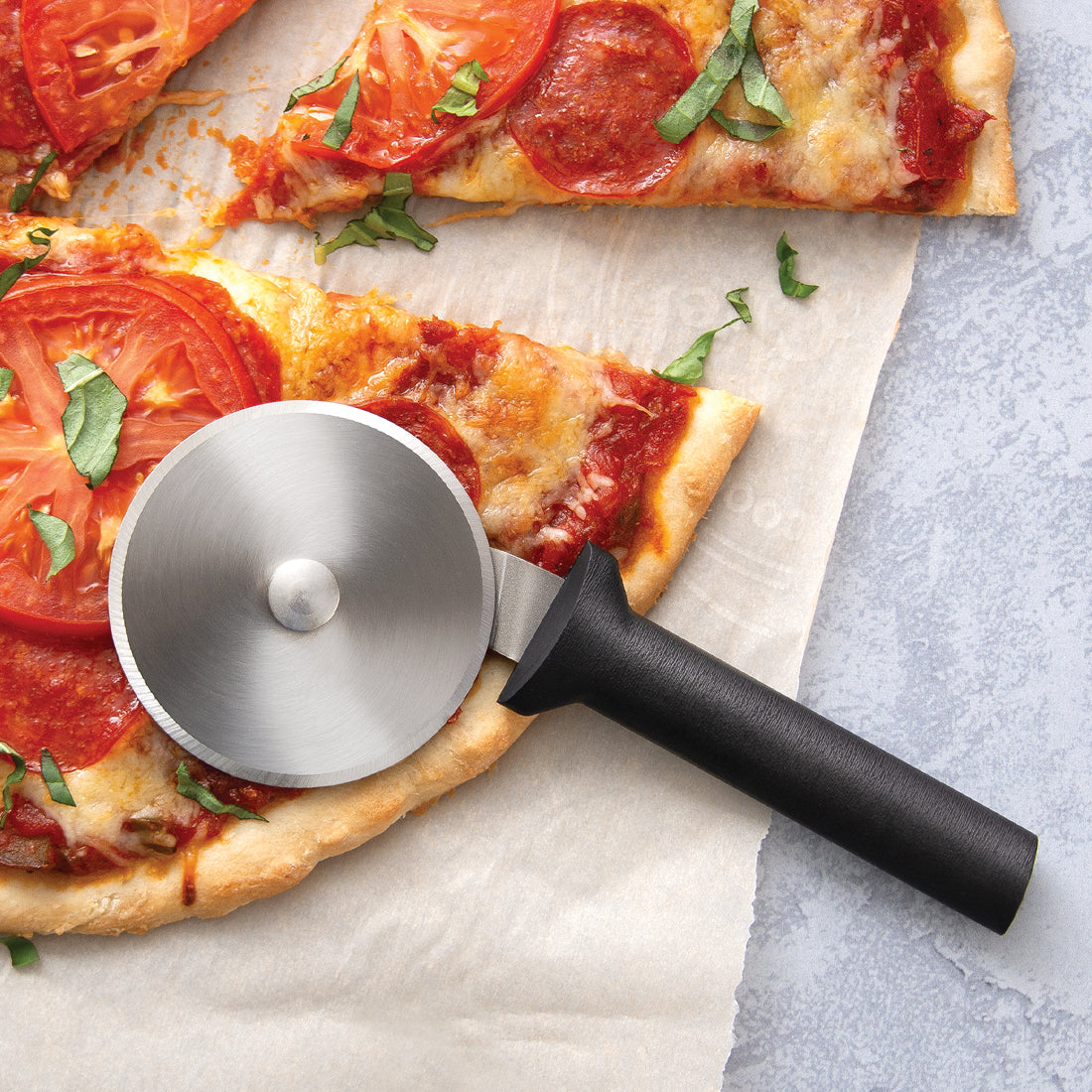 Rada Cutlery pizza cutter with black handle and steel wheel on pizza slice.