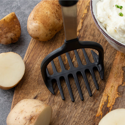 Nonscratch Potato Masher standing upright on cutting board with potatoes.