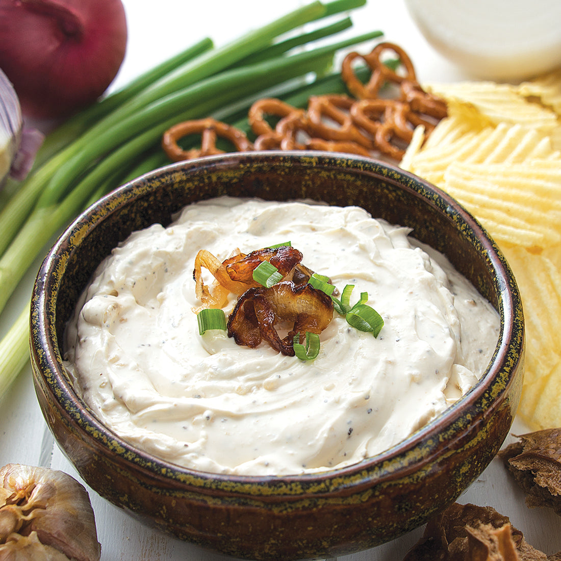 Roasted Garlic and Onion Dip mixed with sour cream and served with chips and pretzels.