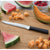 Rada Cutlery Serrated Slicer with silver handle on cutting board with cantaloupe.