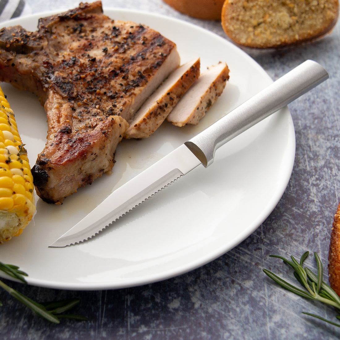Rada Cutlery Serrated Steak knife with silver handle on plate with sliced pork chop.