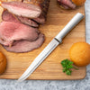 Rada Cutlery Slicer knife with silver handle on cutting board with sliced meat.