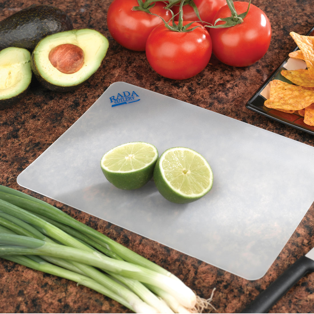 Lime halves on small plastic cutting board with onions, avocados, tomatoes and Rada knife.