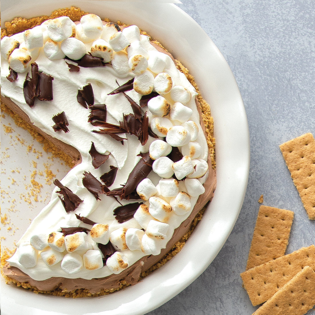S'mores No-Bake Cheesecake in pie dish garnished with chocolate shavings.