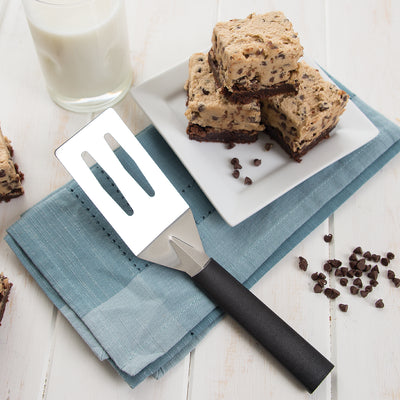 Spatula with black handle on blue napkin by brownies stacked on plate.