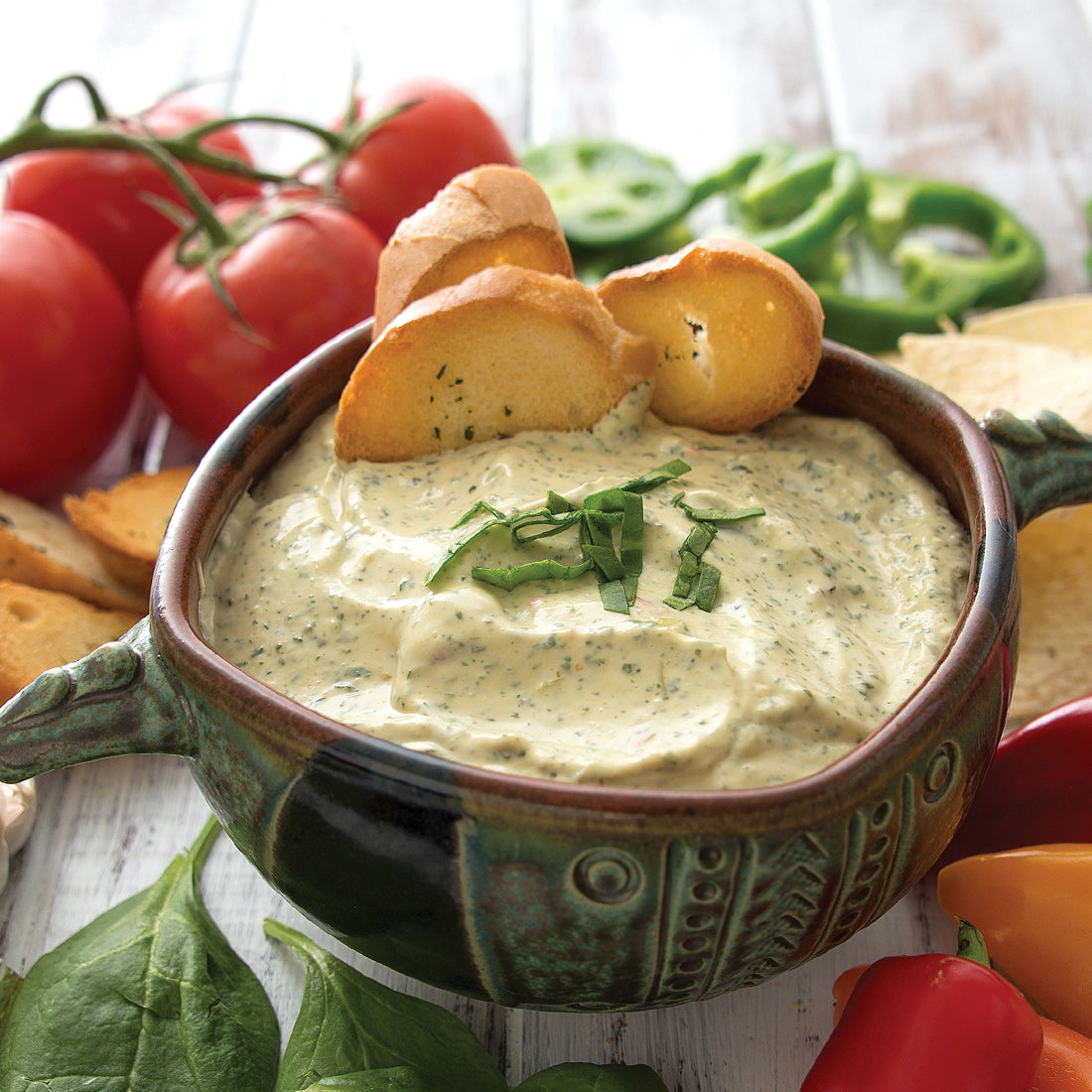 Spinach Artichoke Dip mixed with sour cream and served with veggies.