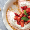 Strawberry Cream No-Bake Cheesecake in pie dish garnished with whipped cream and strawberries.