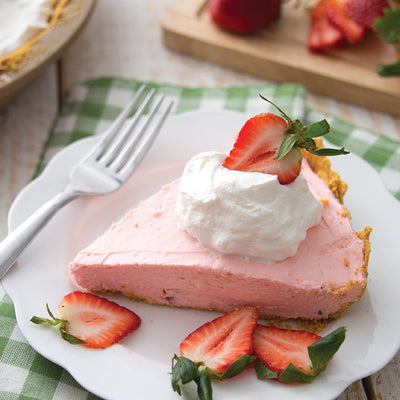 Strawberry Cream No-Bake Cheesecake slice on white plate with strawberries.