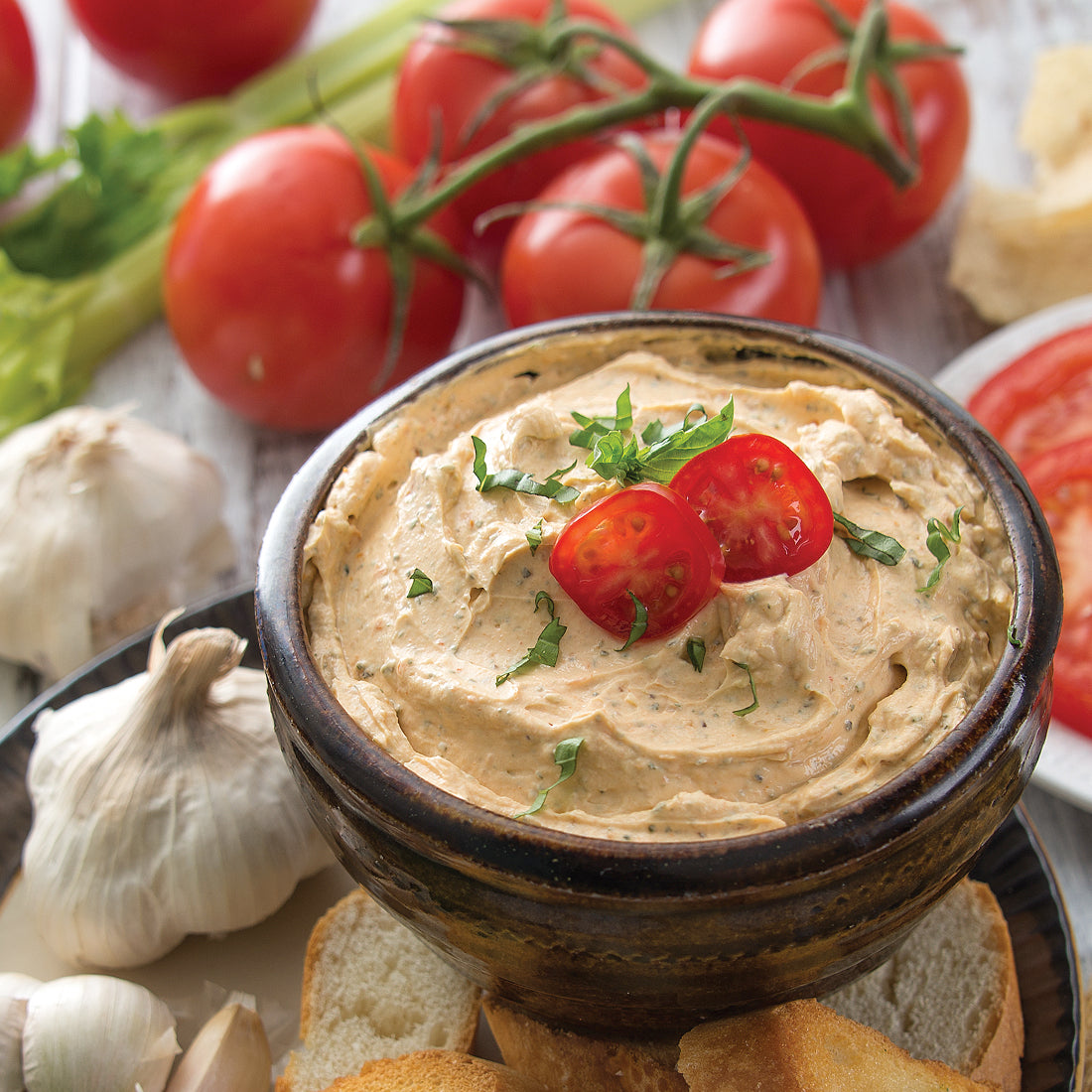 Tomato, Garlic and Basil Dip mixed with sour cream and served with veggies.