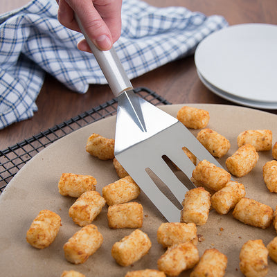 Turnover spatula with silver handle scooping up tator tots.