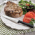 Rada Cutlery Utility Steak knife with black handle on plate with steak, spinach and tomatoes.
