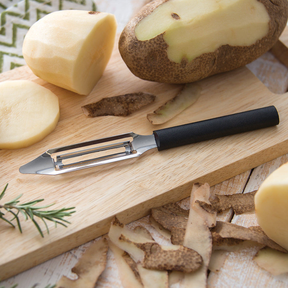 Rada Cutlery Vegetable Peeler with black handle on cutting board with potatoes.
