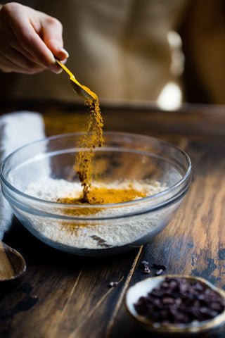person-adding-turmeric-in-glass-bowl-momental-nootropics