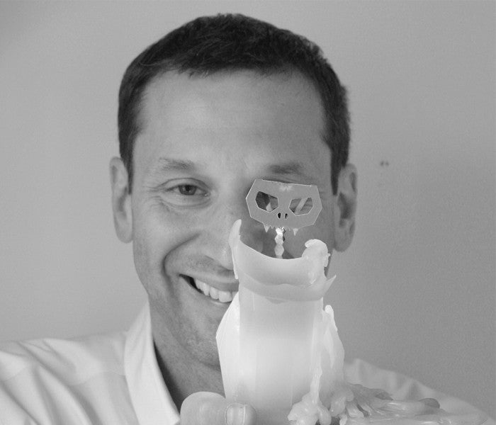 Dan Koval of 54 Celsius holding a burning kisa the cat pyropet candle. As it burns it reveals skeleton frame.