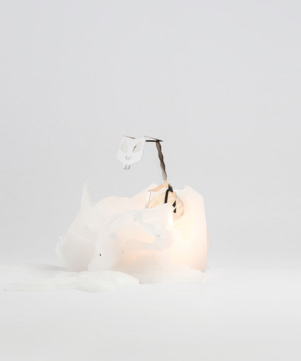 White hoppa pyropet candle was lit and is melting to show the inner skeleton frame inside.