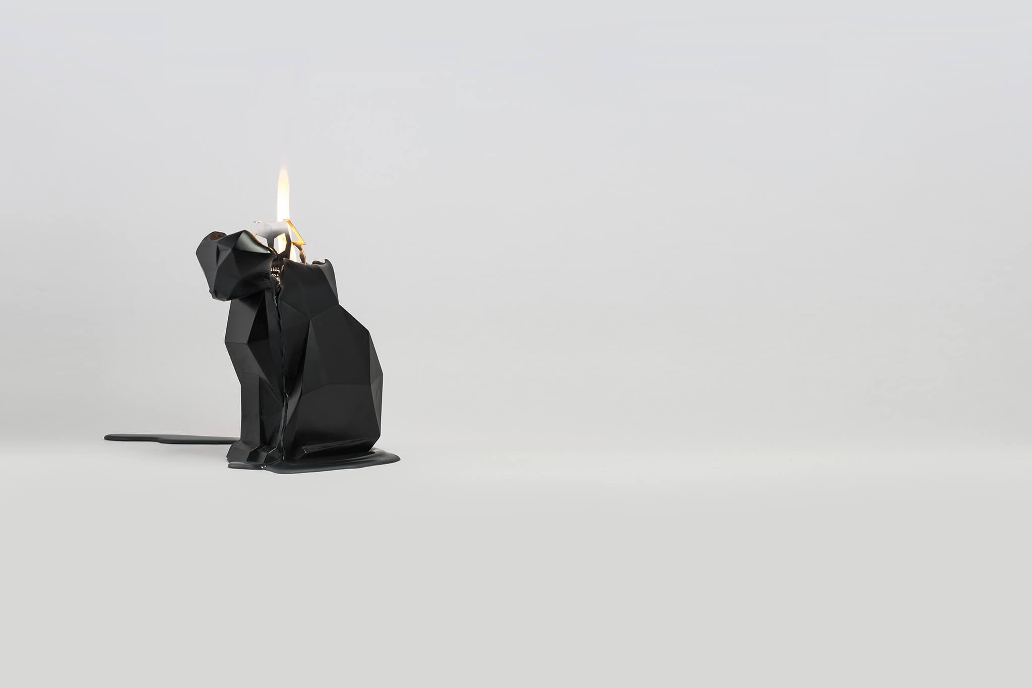 Side view of burning black kisa the cat pyropey candle. Her head is starting to melt.