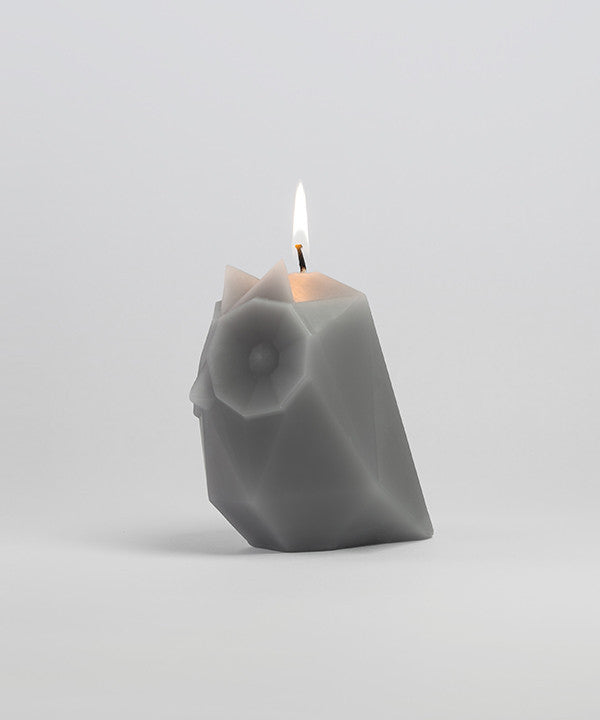 Side view of burning Ugla Owl shaped pyropet candle in grey.