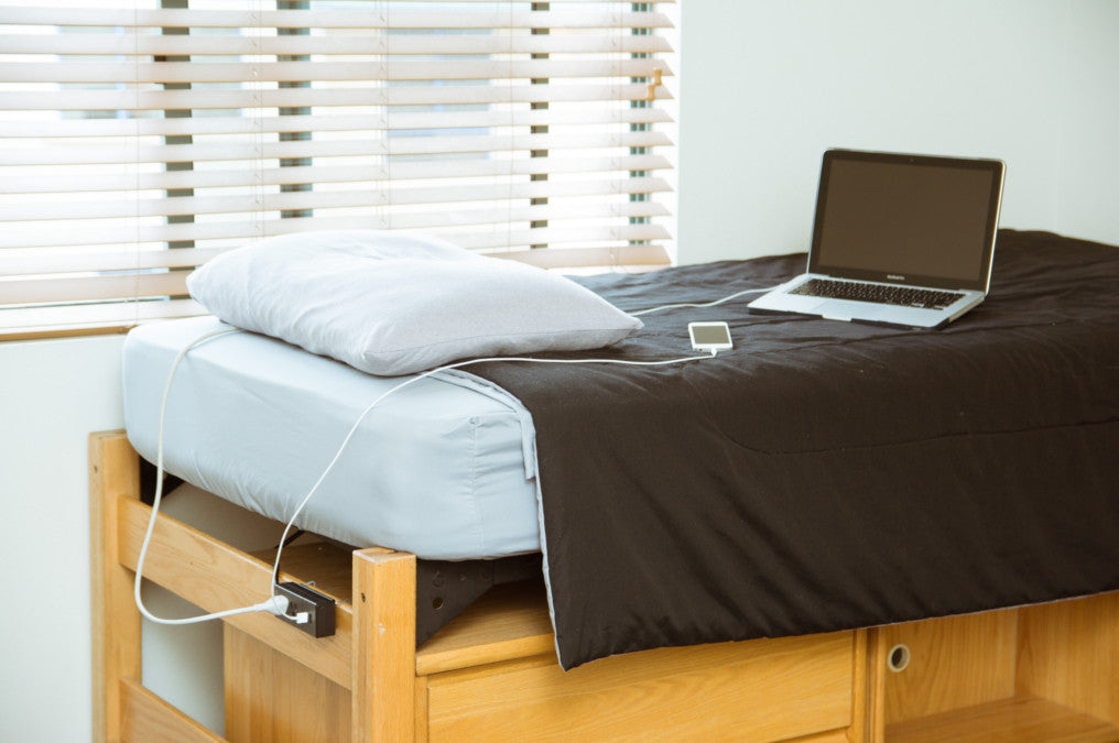 Image of a BedPower attached to a College Dorm Bed with computer and Cell Phone