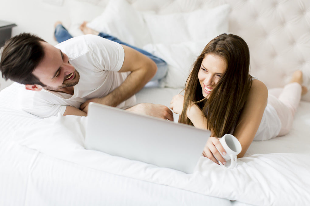 Image of a happy couple using their computer while in bed. BedPower