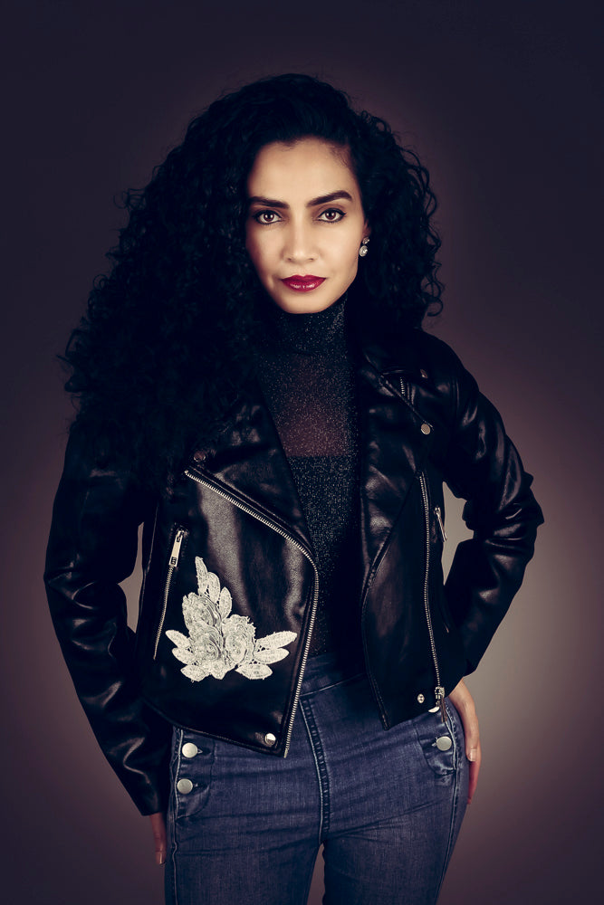 Umayya Theba wearing a black biker jacket embellished with silver roses