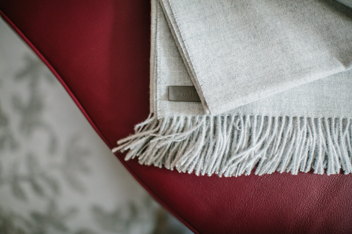 AUTHOR Luxury Natural Grey Alpaca Wool Throw on Burgundy AUTHOR Deer Hide Wilf Chair