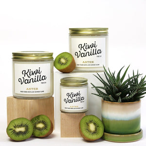 Large and mini Kiwi Vanilla scented soy candles pictured with sliced kiwis and succulent.