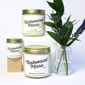 Large and mini Teakwood Moss scented soy candles pictured with bud vase and greenery.