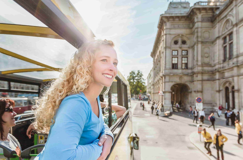 A girl sitting on the Hop on hop off bus while taking a tour  in Vienna
