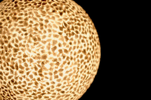 Detailed close up on gold mother of pearl finish of globe lamp. Callisto by Collectiviste lighting