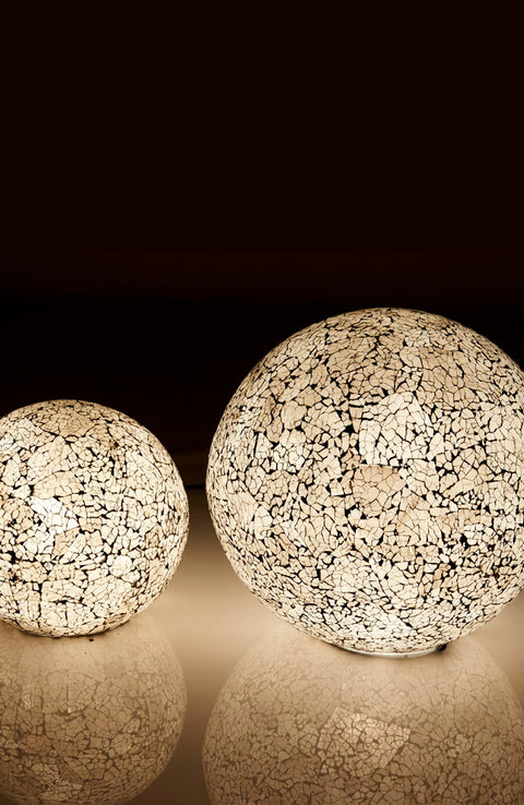Amalthea globe lamps in the dark with reflections by Collectiviste. Handcrafted black and white frosted white glass globe lamp in 2 sizes (ON)