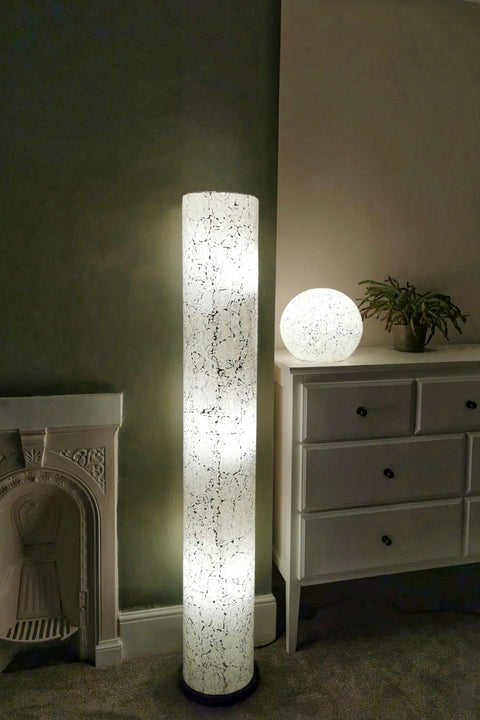 Amalthea white glass globe lamp and floor lamp at night.