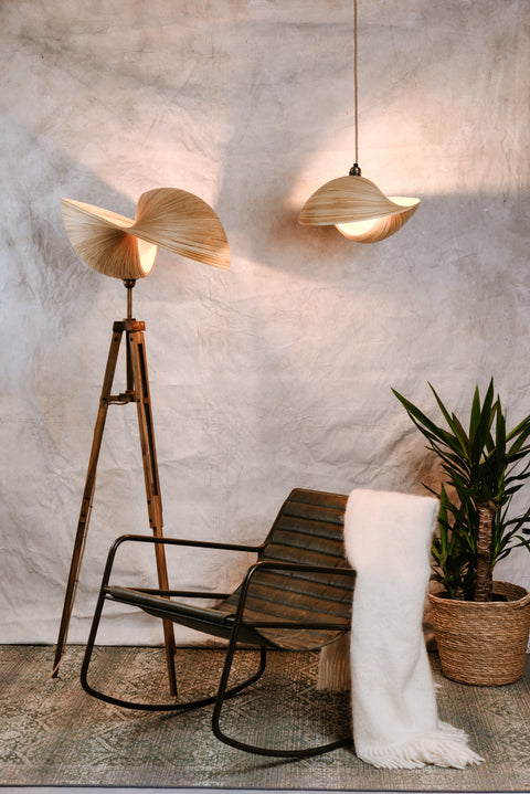 Large bamboo tripod floor lamp and bamboo ceiling pendant beside green leather rocking chair. Kyoto bamboo lighting collection by Collectiviste.