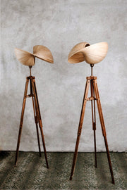 Teak wooden tripod standing lamps with bamboo lampshades.