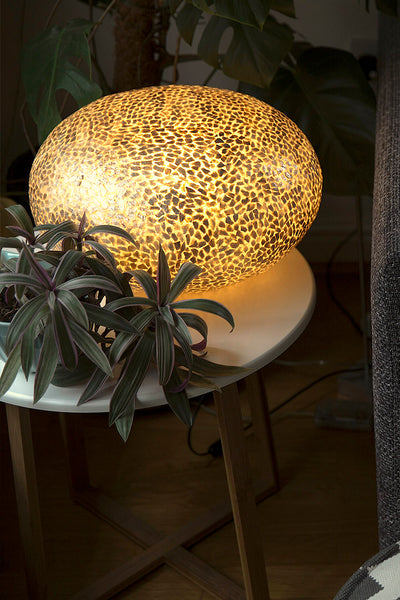 Unusual oval shaped table lamp. Handcrafted from gold oyster shells. Modern decorative lighting by Collectiviste.