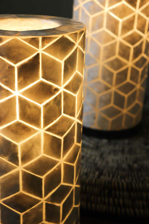 Close up of Pair of white oyster shell table lamps in geometric diamond design. Cube design. Light On