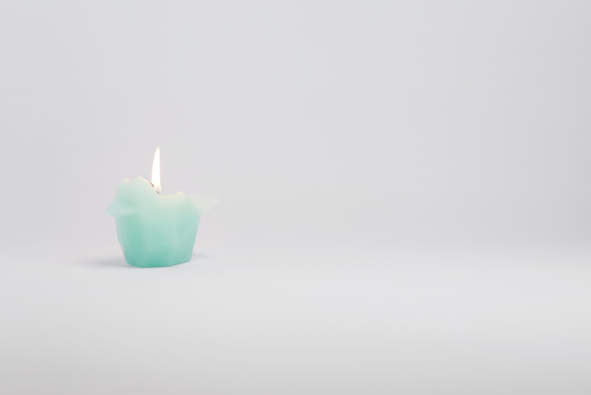 Side view of mint bird shaped pyropet candle that has a burning wick.