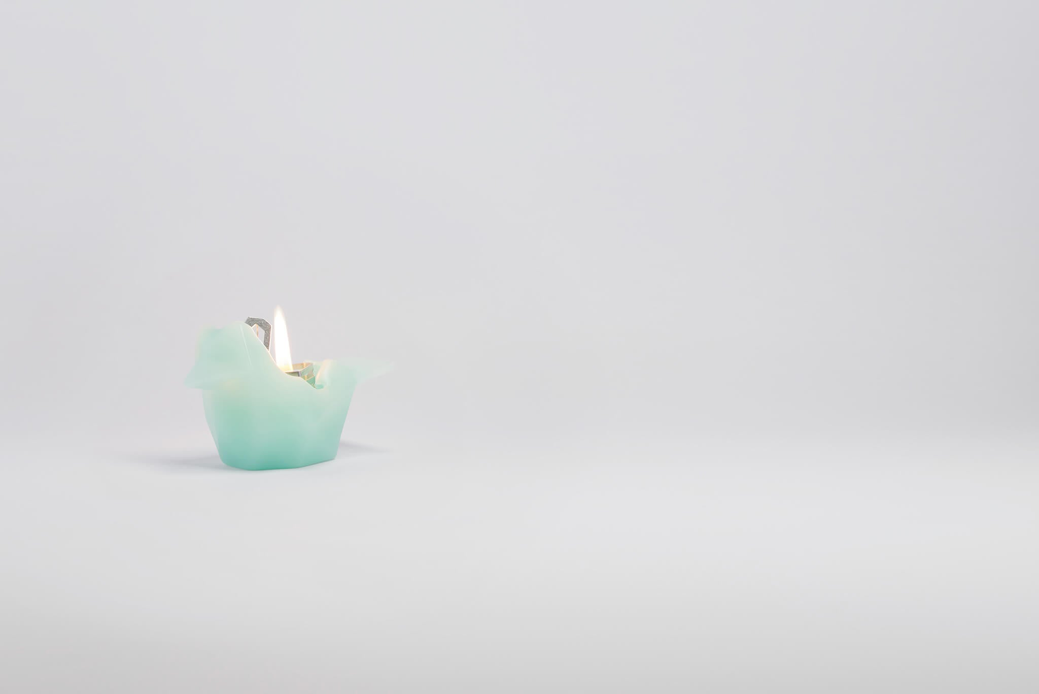 Side view of burning mint bird shaped candle. As the wax melts a metal skeleton frame is revealed.
