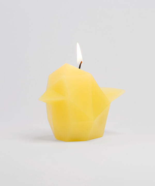 Side view of vibrant yellow bird shaped pyropet candle that has a lit wick.