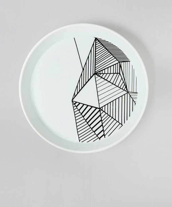 Top view of white and black geometric porcelain candle plate.