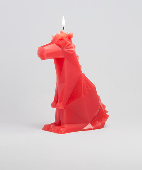 Side view of red dreki propet dragon candle. The wick is lit.