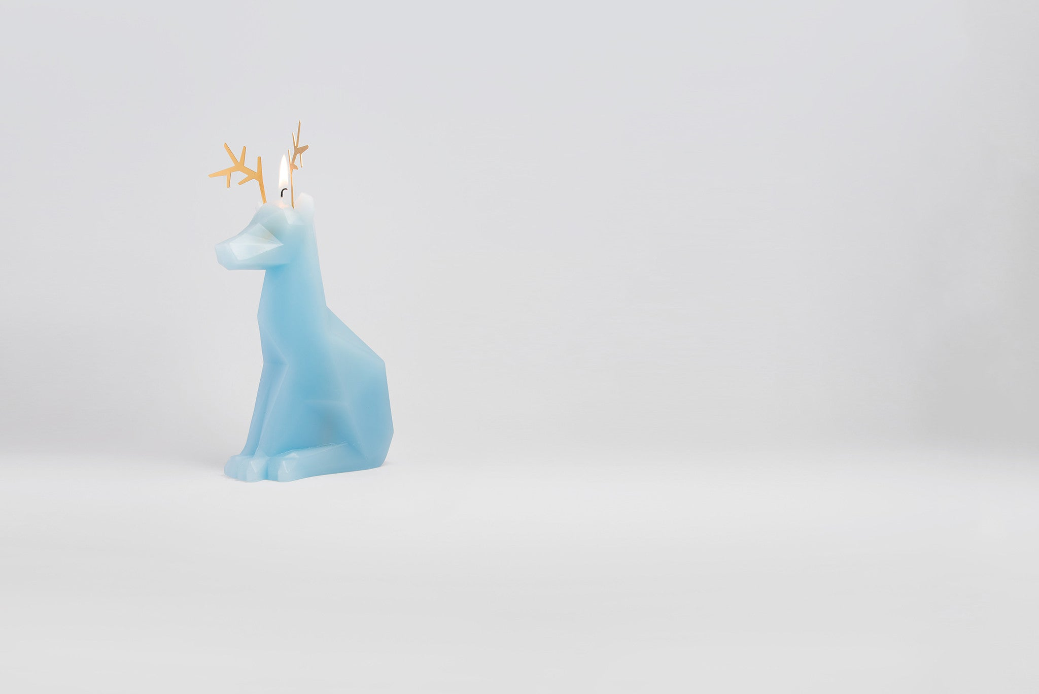 Side view of light blue dyri reindeer animal candle with the wick burning.