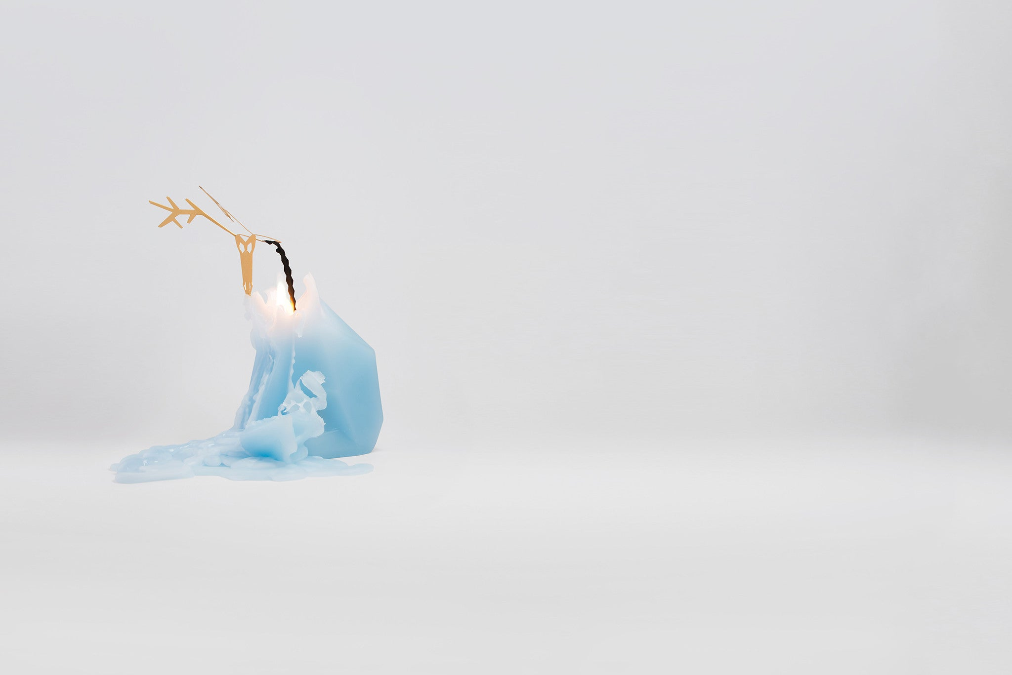 Side view of melting light blue reindeer pyropet candle. As the wax melts, the candle reveals an inner skelton frame.